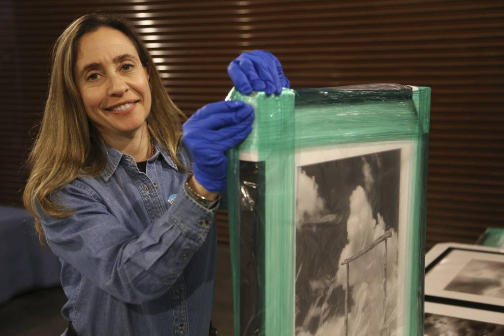 Tricia Loscher, assistant director and chief curator at Scottsdale's Museum of the West, smiles as she carefully unpacks a framed photograph taken by ...
