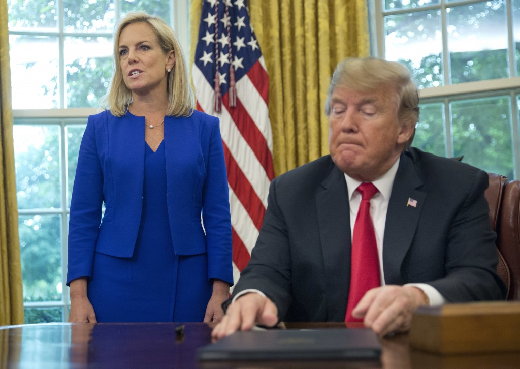 FILE - In this June 20, 2018, file photo, President Donald Trump, right, listens as Homeland Security Secretary Kirstjen Nielsen, left, addresses memb...