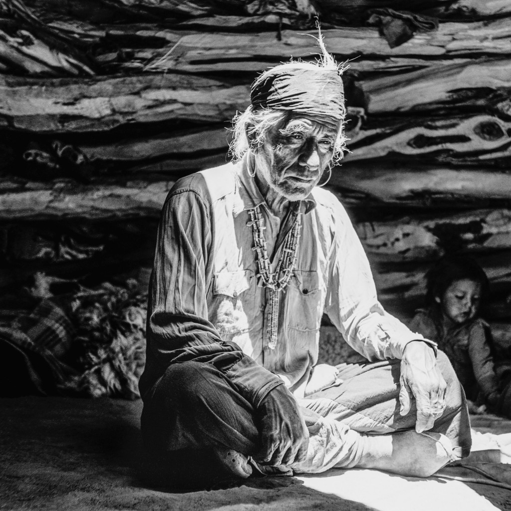 This photograph taken by Barry Goldwater in 1948 on the north side of Navajo Mountain in Arizona shows an elderly man sitting cross-legged and illumin