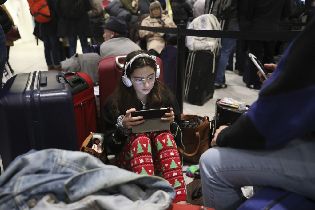Passengers at Gatwick airport settle down to wait for their flights following the delays and cancellations brought on by drone sightings near the airf