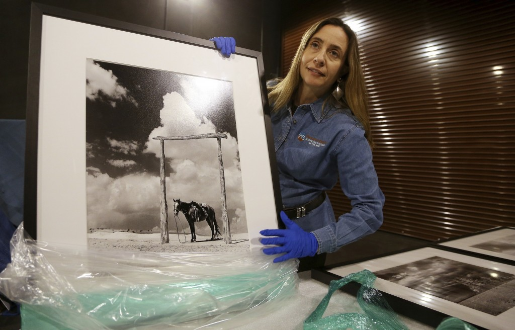 Tricia Loscher, assistant director and chief curator at Scottsdale's Museum of the West, carefully unpacks a framed photograph taken by former Arizona...