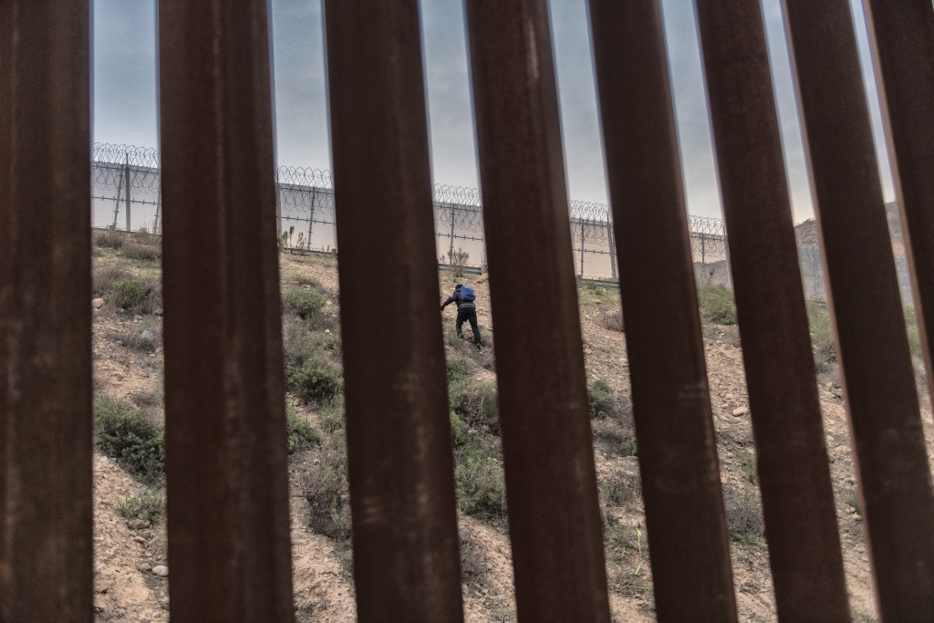 A Honduran migrant w climbs an embankment after jumping over the U.S. border wall from Tijuana, Mexico, to San Diego, Calif., as seen from Tijuana, Me...