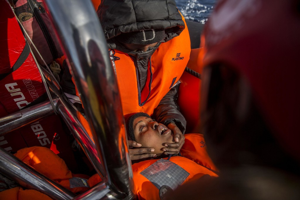 In this Friday, Dec. 21, 2018, photo, a woman faints after being rescued by aid workers of Spanish NGO Proactiva Open Arms, in the Central Mediterrane