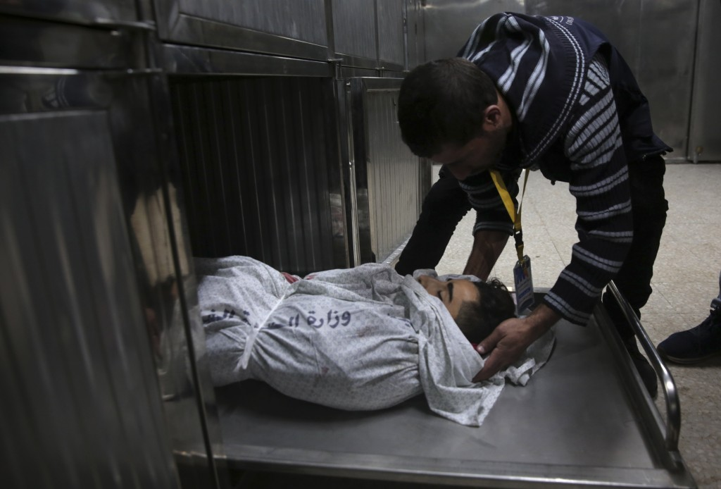 A medic checks the body of 16-year-old Mohammed Jahjouh, who was shot and killed by Israeli troops during a protest at the Gaza Strip's border with Is