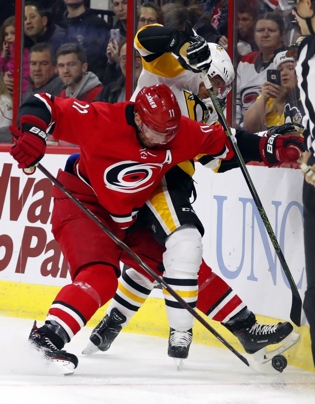 Carolina Hurricanes' Jordan Staal (11) tussles with Pittsburgh Penguins' Sidney Crosby (87) during the first period of an NHL hockey game, Saturday, D