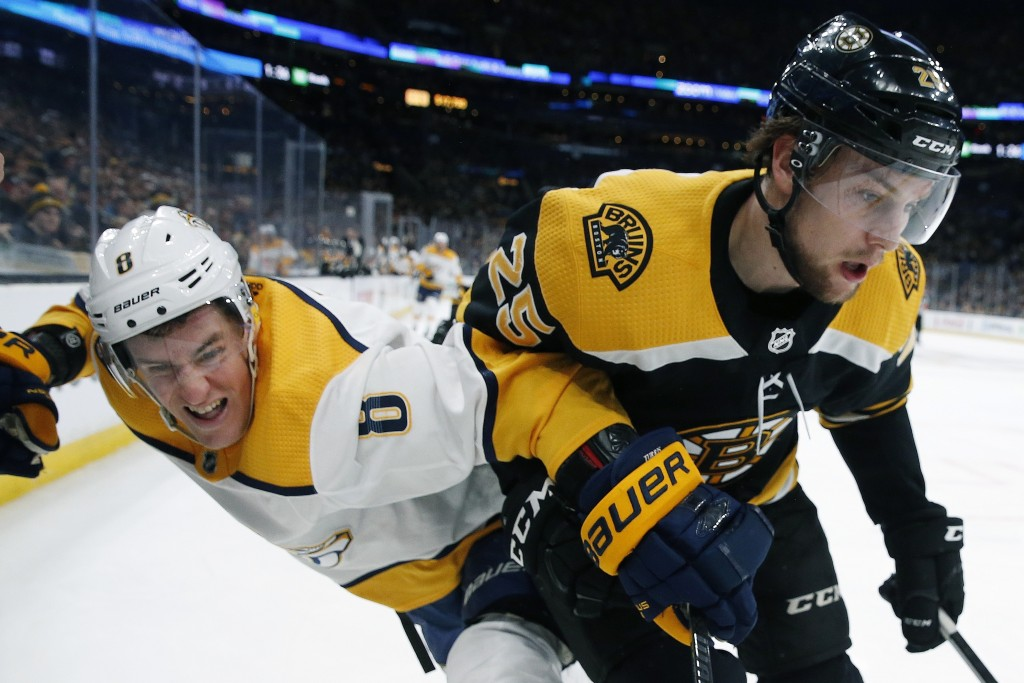 Nashville Predators' Kyle Turris (8) and Boston Bruins' Brandon Carlo (25) battle for the puck during the first period of an NHL hockey game in Boston...