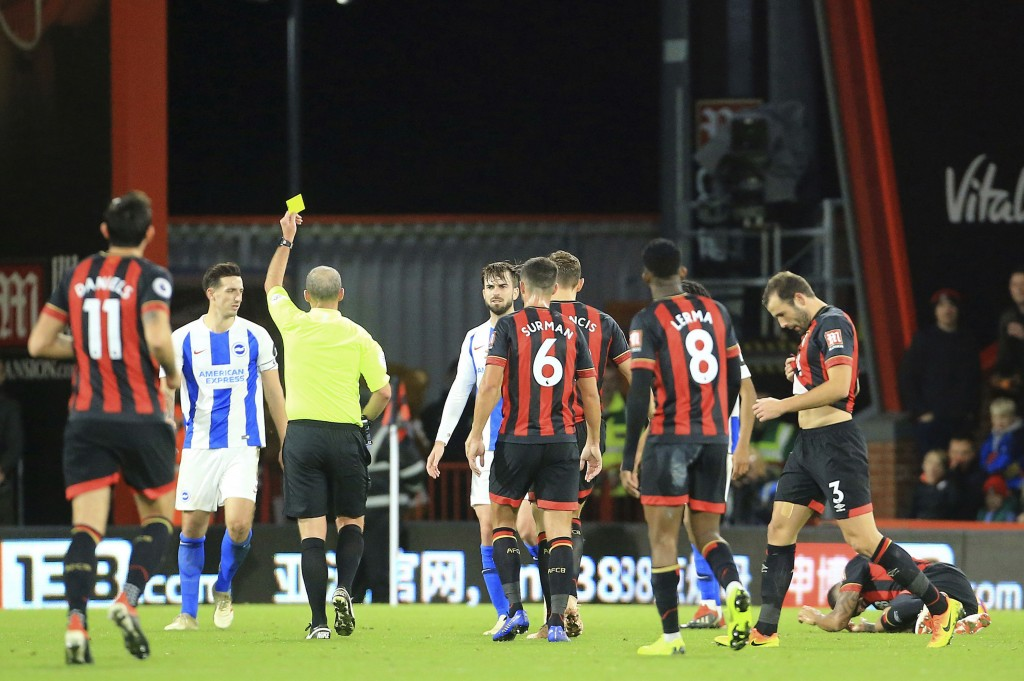 Brighton & Hove Albion's Lewis Dunk, second left, is sent off the pitch after being shown his second yellow card by match referee Mike Dean, center. d...