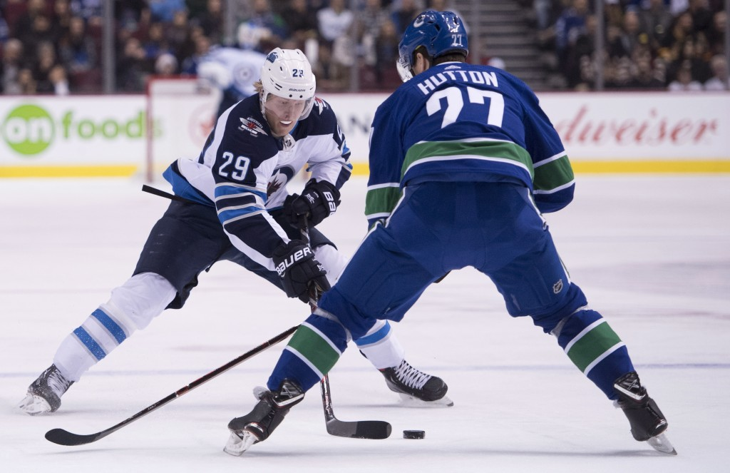 Winnipeg Jets right wing Patrik Laine (29) tries to get the puck past Vancouver Canucks defenseman Ben Hutton (27) during first-period NHL hockey game...