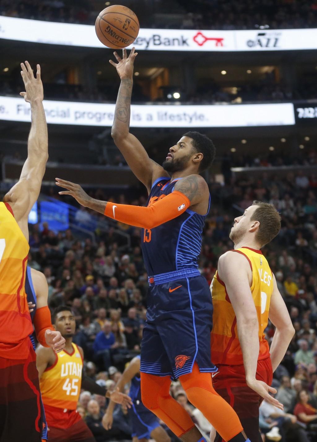 Oklahoma City Thunder forward Paul George, center, shoots as Utah Jazz forward Joe Ingles, right, defends in the first half of an NBA basketball game,...