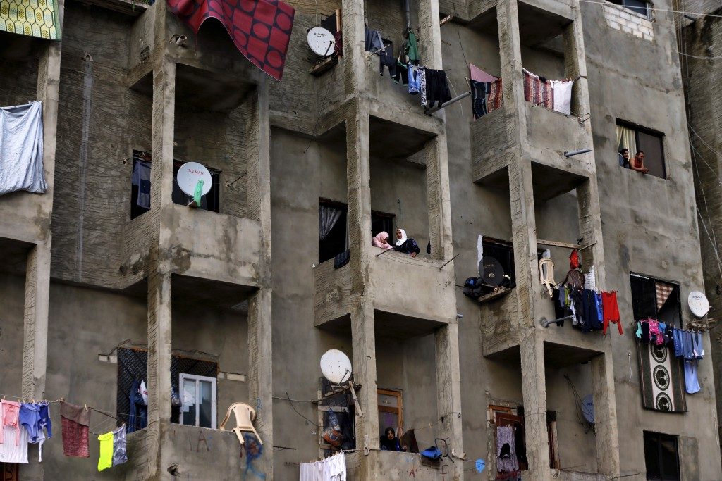 In this Tuesday, Dec. 18, 2018, photo, Syrian refugees stand on their balcony at Ouzai refugee compound in the southern port city of Sidon, Lebanon. A...