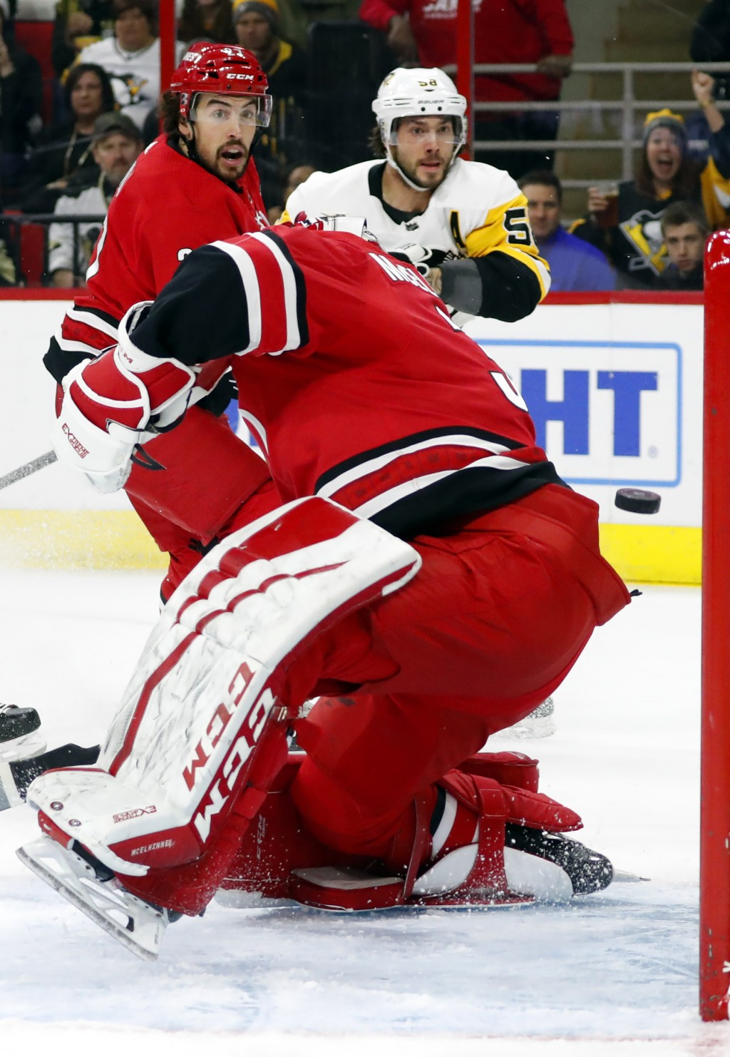 Pittsburgh Penguins' Kris Letang (58) and Carolina Hurricanes' Justin Faulk (27) watch the puck come out of the net after Letang got it past goaltende...
