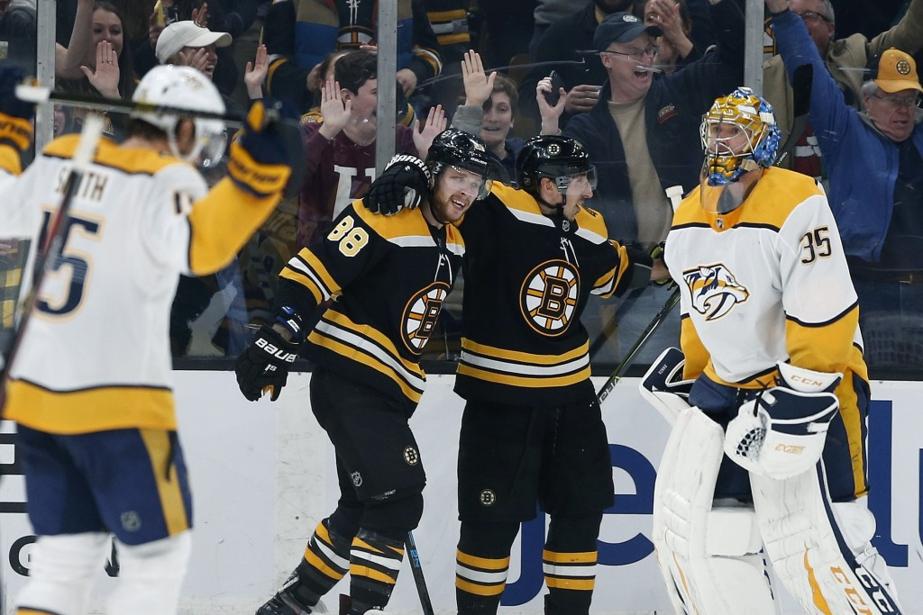 Boston Bruins' David Pastrnak (88) celebrates his goal on Nashville Predators' Pekka Rinne (35) with teammate Brad Marchand, center right, during the ...