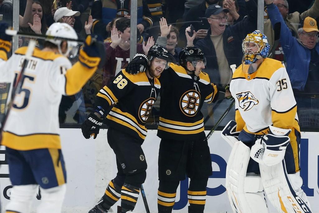 Boston Bruins' David Pastrnak (88) celebrates his goal on Nashville Predators' Pekka Rinne (35) with teammate Brad Marchand, center right, during the
