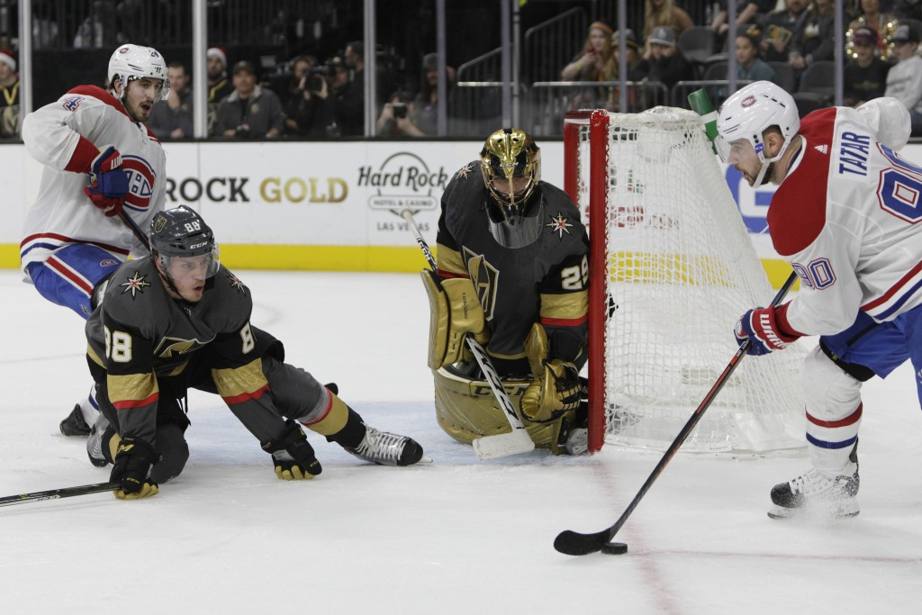 Vegas Golden Knights defenseman Nate Schmidt (88) and goaltender Marc-Andre Fleury (29) try to hold off pressure from Montreal Canadiens' Tomas Tatar,