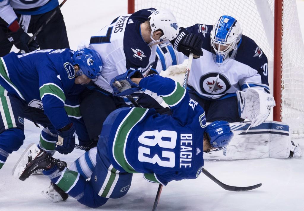 Winnipeg Jets defenseman Tyler Myers (57) stops Vancouver Canucks center Jay Beagle (83) from getting a shot on Winnipeg Jets goaltender Laurent Bross...