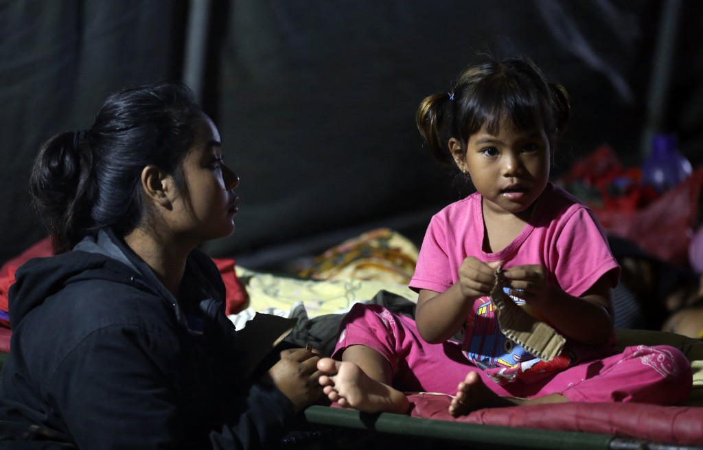 Tsunami survivors sit at temporary shelter in Tanjung Lesung, Indonesia, Sunday, Dec. 23, 2018. The tsunami occurred after the eruption of a volcano a...