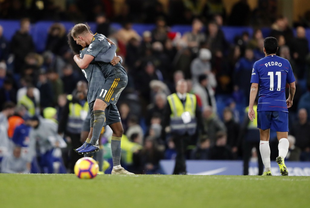 Leicester's Marc Albrighton and Leicester's Hamza Choudhury, left, celebrate as Chelsea's Pedro walks out in dejection after they won the English Prem...