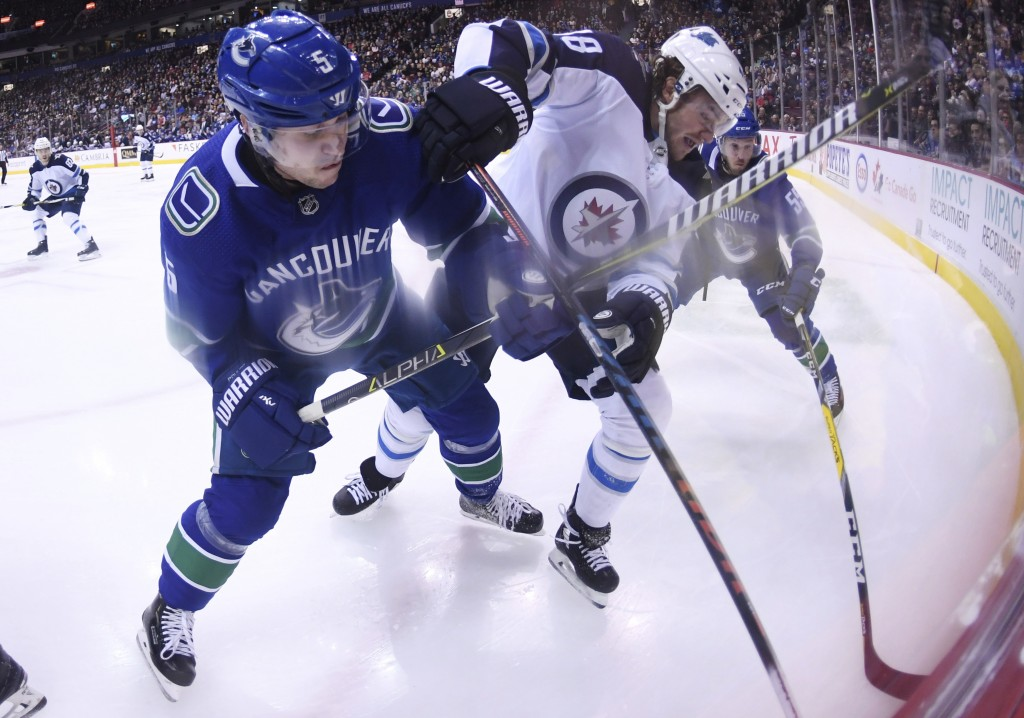 Vancouver Canucks defenseman Derrick Pouliot (5) fights for control of the puck with Winnipeg Jets left wing Brendan Lemieux (48) during first-period ...