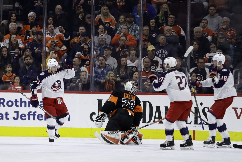 Columbus Blue Jackets' Cam Atkinson (13) celebrates with Ryan Murray (27) and Pierre-Luc Dubois (18) after scoring a goal past Philadelphia Flyers' Ca