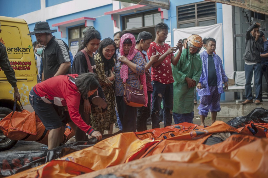 In this Sunday, Dec. 23, 2018, photo, People search for relatives among the bodies of tsunami victims in Carita, Indonesia. The tsunami that hit the c...