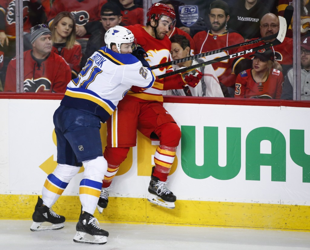 St. Louis Blues' Tyler Bozak, left, checks Calgary Flames' T.J. Brodie during the second period of an NHL hockey game Saturday, Dec. 22, 2018, in Calg