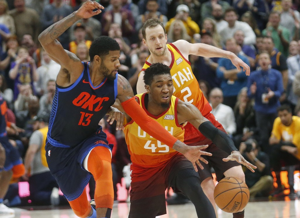 Utah Jazz guard Donovan Mitchell (45) steals the ball from Oklahoma City Thunder forward Paul George (13) in the second half during an NBA basketball ...