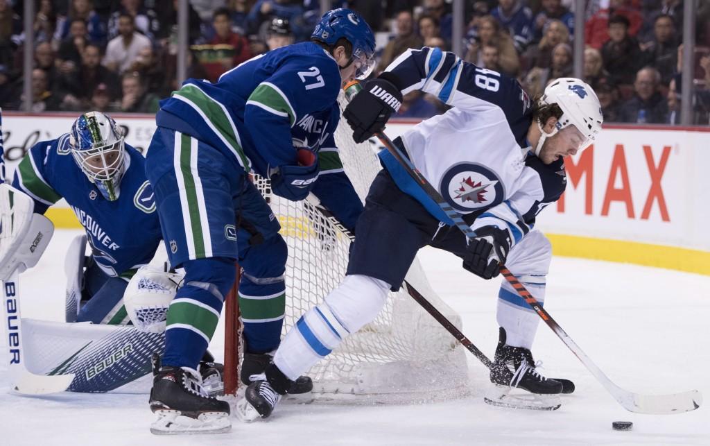 Vancouver Canucks defenseman Ben Hutton (27) tries to keep Winnipeg Jets left wing Brendan Lemieux (48) from getting a shot against Canucks goaltender...