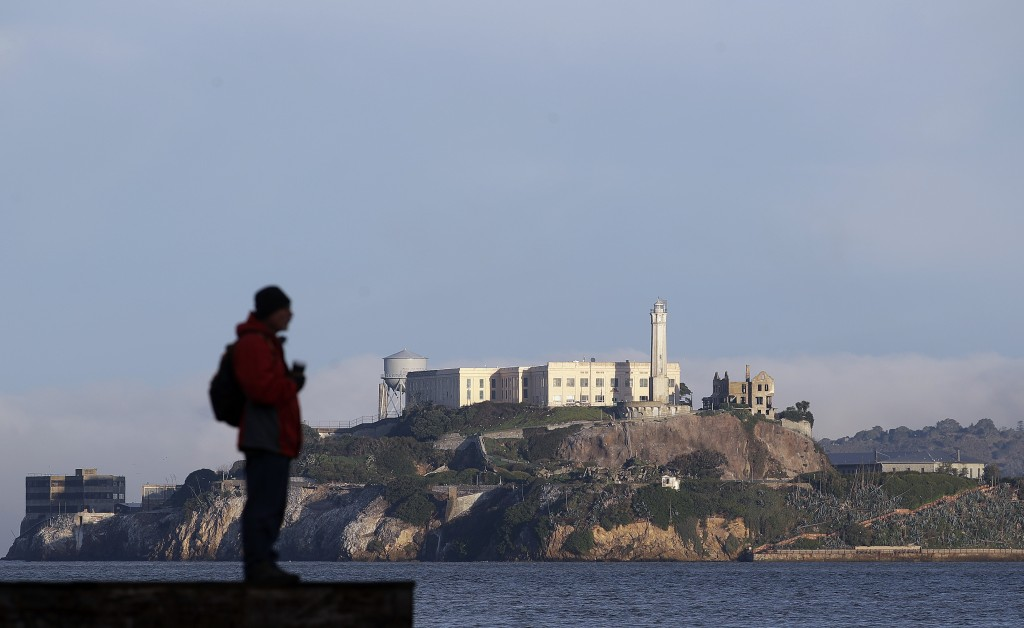 A man stands on a pier with Alcatraz Island at rear in San Francisco, Saturday, Dec. 22, 2018. A partial federal shutdown has been put in motion becau