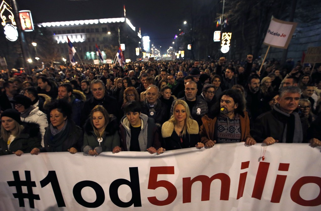 People hold a banner that reads: ''#1out of 5 million'' during a protest against populist President Aleksandar Vucic in Belgrade, Serbia, Saturday, De