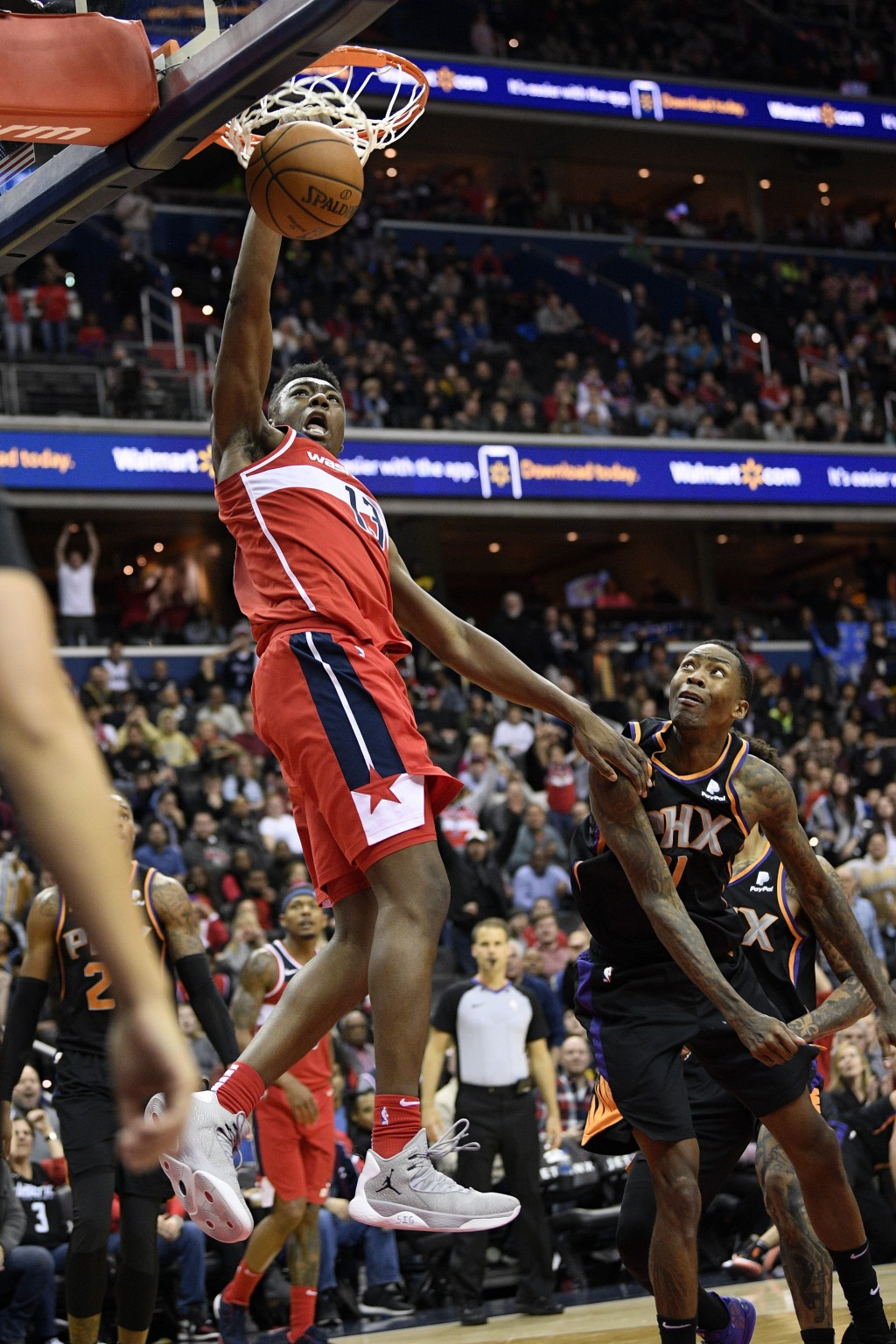 Washington Wizards center Thomas Bryant (13) dunks over Phoenix Suns guard Jamal Crawford, right, during triple overtime of an NBA basketball game, Sa...