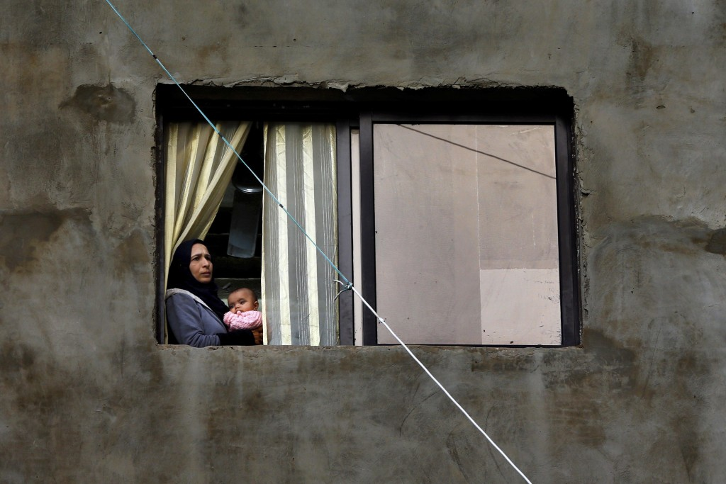 In this Tuesday, Dec. 18, 2018, photo, a Syrian refugee looks through a window as she holds her daughter in Ouzai refugee compound, in the southern po...