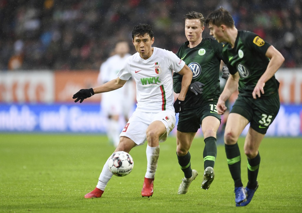 Wolfsburg's Yannick Gerhardt, center, and Augsburg's Ja-Cheol Koo, left, challenge for the ball during the German Bundeliga soccer match between FC Au...