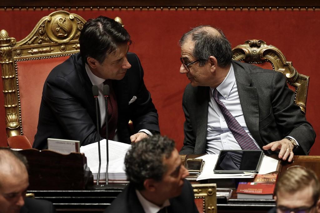 In this picture taken Saturday, Dec. 22, 2018, Italian Prime Minister Giuseppe Conte, left, talks to Italian Economy Minister Giovanni Tria prior to t...