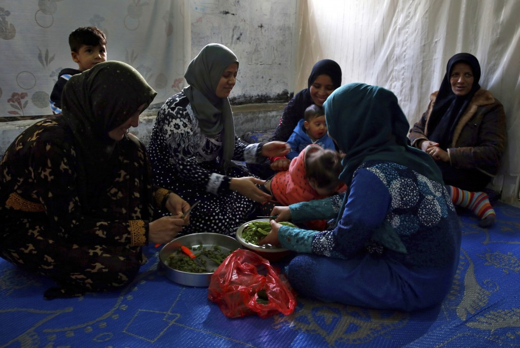 In this Tuesday, Dec. 18, 2018, photo, Syrian refugees women prepare lunch in Ouzai refugee compound, in the southern port city of Sidon, Lebanon. A m...