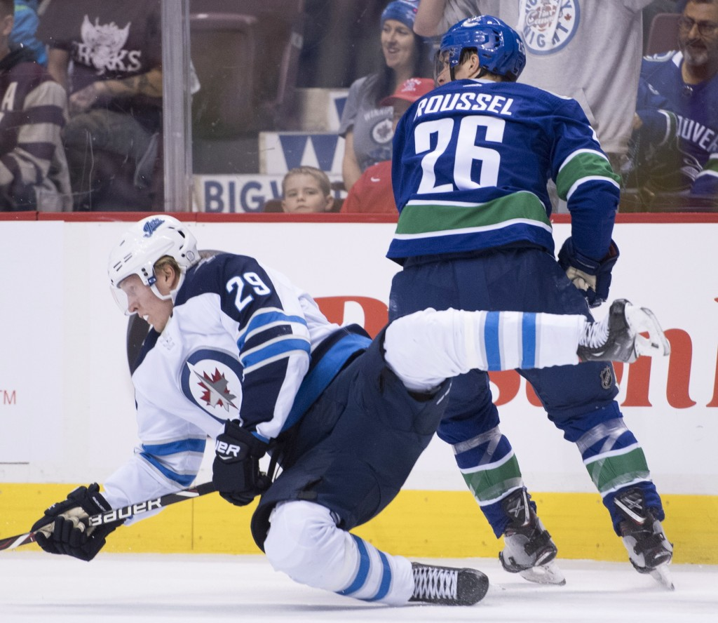Winnipeg Jets right wing Patrik Laine (29) fights for control of the puck with Vancouver Canucks left wing Antoine Roussel (26) during first-period NH...