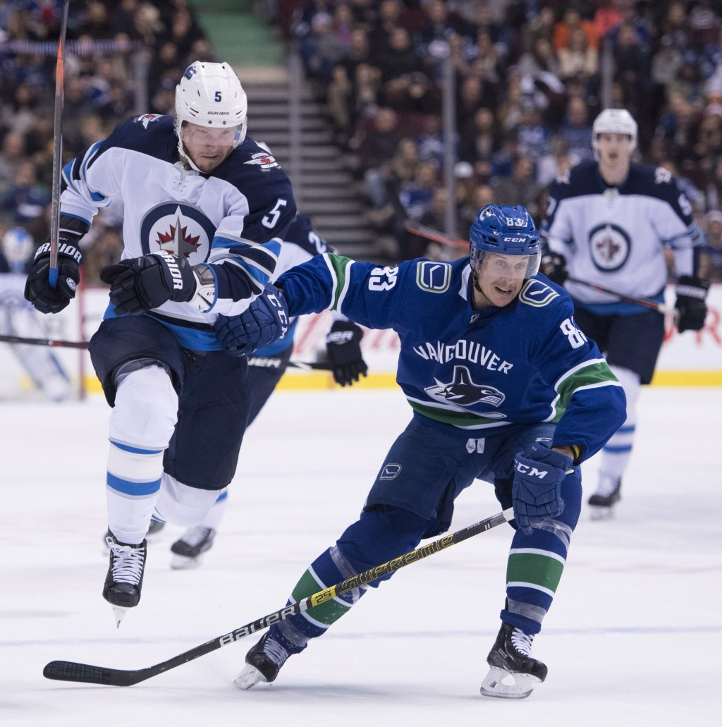Winnipeg Jets defenseman Dmitry Kulikov (5) fights for control of the puck with Vancouver Canucks center Jay Beagle (83) during first-period NHL hocke...