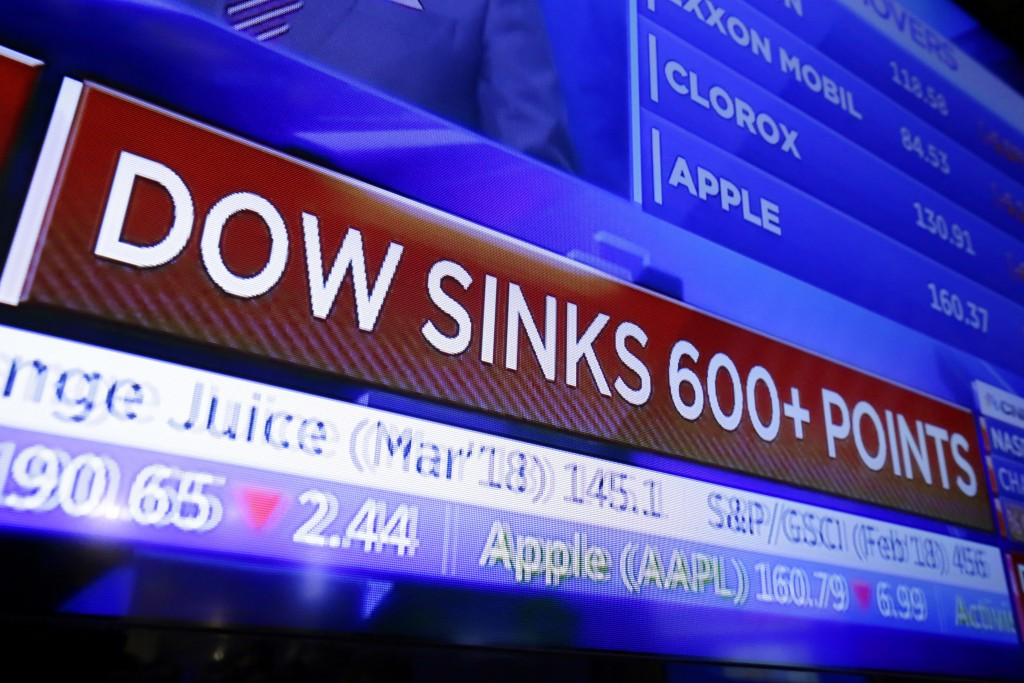 FILE - In this Feb. 2, 2018, file photo, a television screen displays the Dow Jones industrial average story, on the floor of the New York Stock Excha