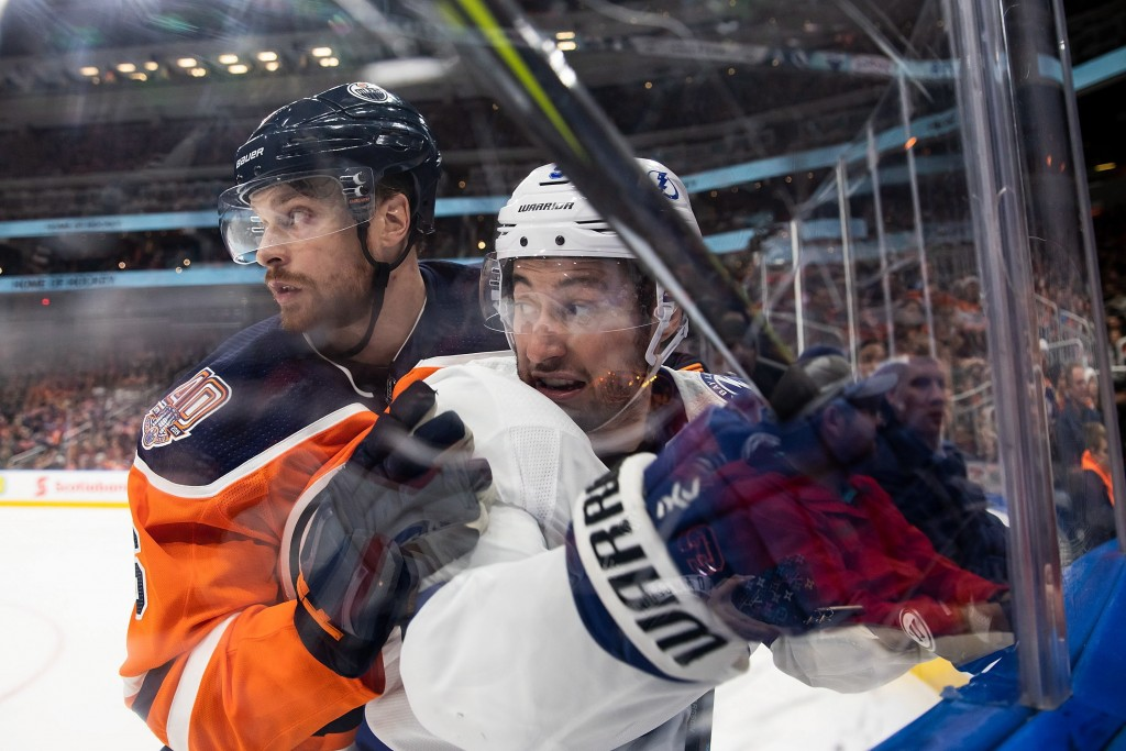 Edmonton Oilers defenseman Adam Larsson (6) holds Tampa Bay Lightning center Tyler Johnson (9) against the boards during the third period of an NHL ho...