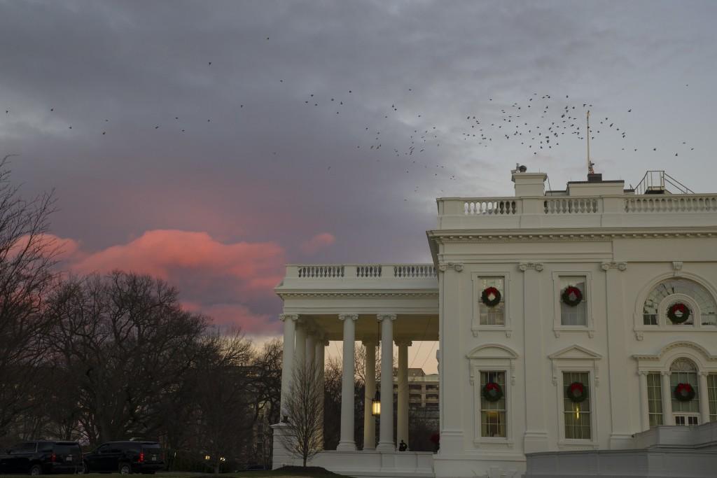 The setting sun illuminates clouds behind the White House during a partial federal shutdown, Saturday, Dec. 22, 2018, in Washington. The partial feder...