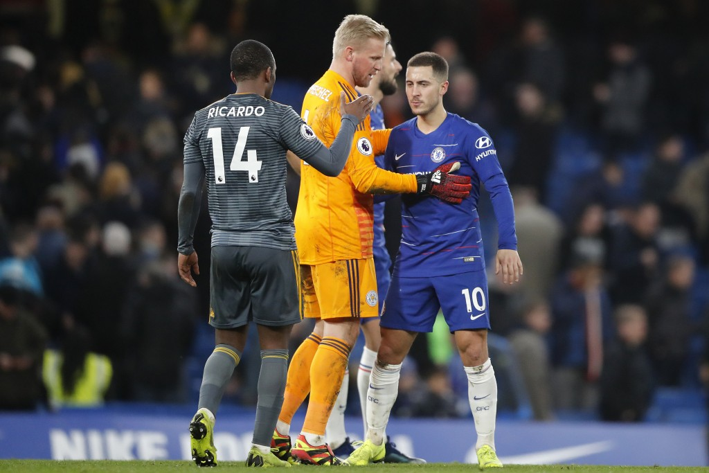 Chelsea's Eden Hazard, right, is comforted by Leicester's goalkeeper Kasper Schmeichel, center, and Leicester's Ricardo, right, after they won the Eng...