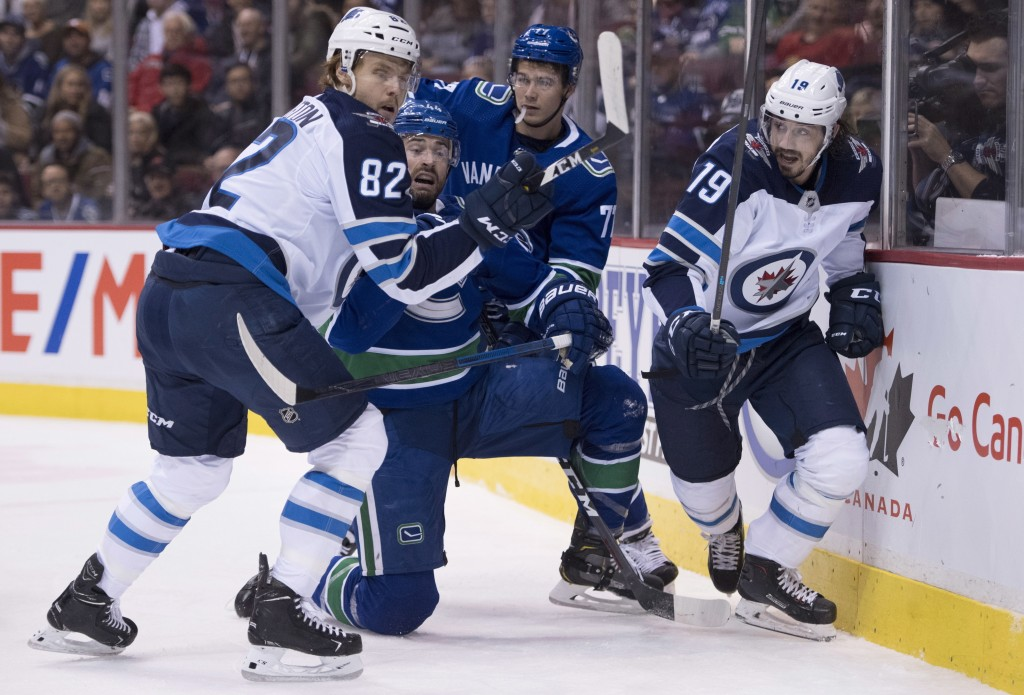 Vancouver Canucks defenseman Erik Gudbranson (44) fights for control of the puck with Winnipeg Jets center Mason Appleton (82) and left wing Nic Petan...