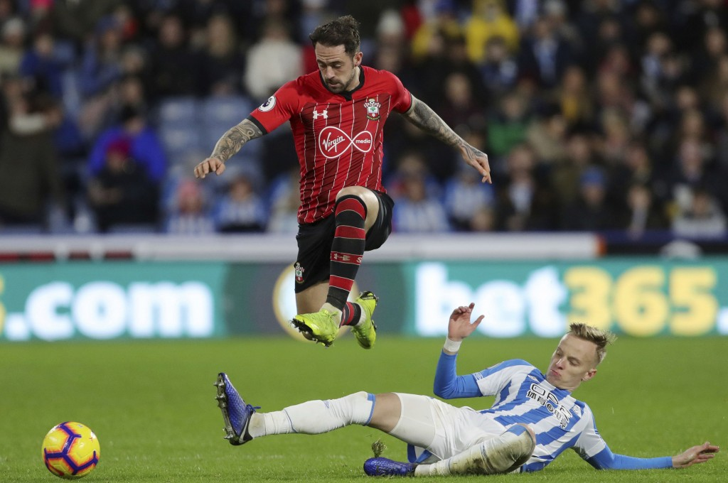 Southampton's Danny Ings, top, rides a challenge from Huddersfield Town's Florent Hadergjonaj during the English Premier League soccer match between H