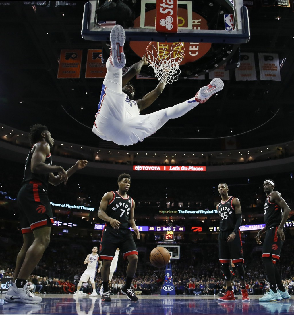 Philadelphia 76ers' Joel Embiid, top, hangs on the rim after a dunk during the first half of an NBA basketball game against the Toronto Raptors, Satur