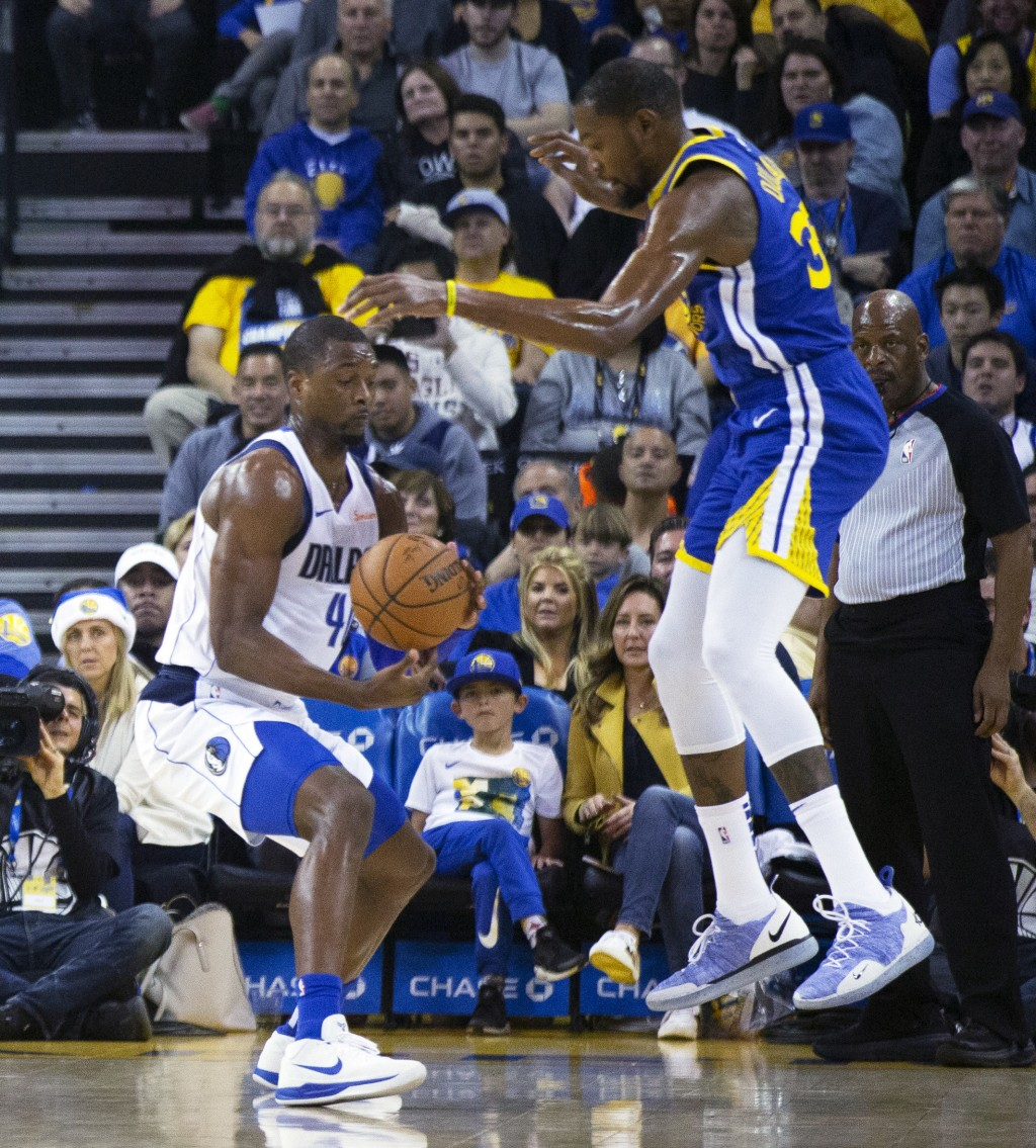 Dallas Mavericks' Harrison Barnes (40) steals the ball from Golden State Warriors' Kevin Durant (35) during the first quarter of an NBA basketball gam...