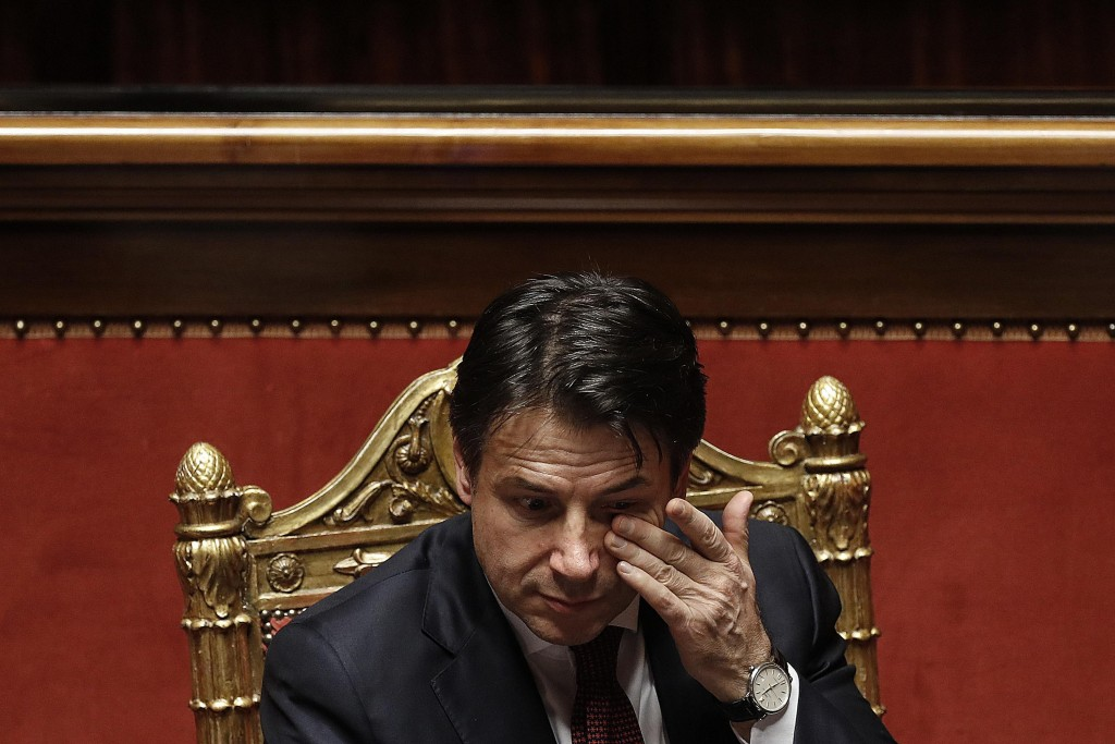 In this picture taken Saturday, Dec. 22, 2018, Italian Prime Minister Giuseppe Conte touches his eye prior to the start of a confidence vote on the bu