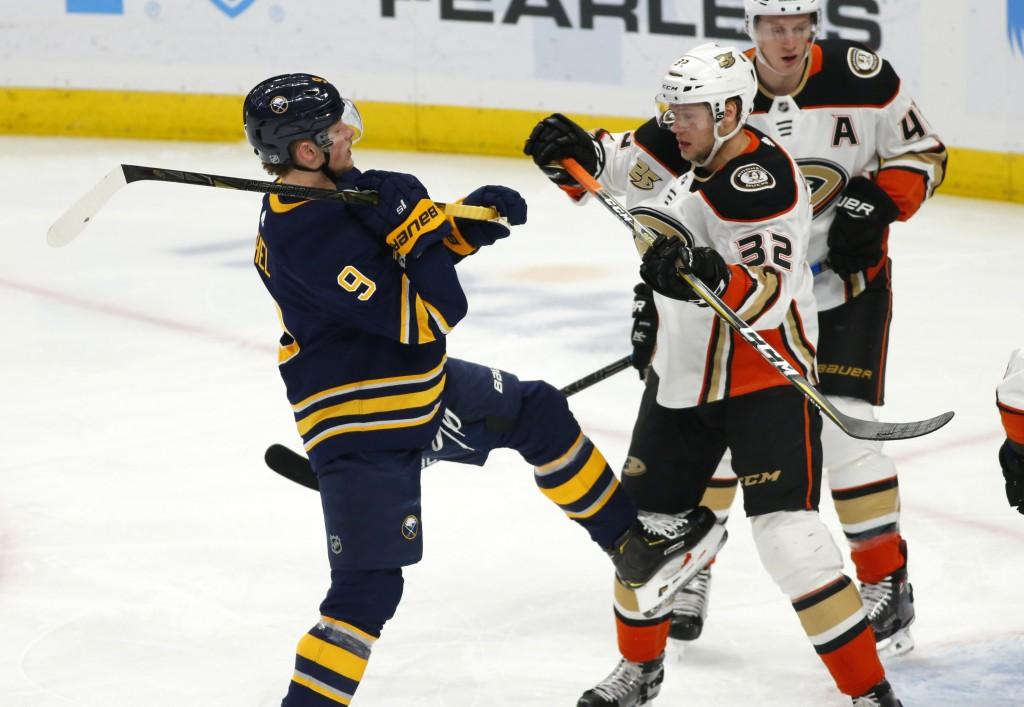 Buffalo Sabres forward Jack Eichel (9) and Anaheim Ducks defenseman Jacob Larsson (32) battle during the first period of an NHL hockey game, Saturday,...