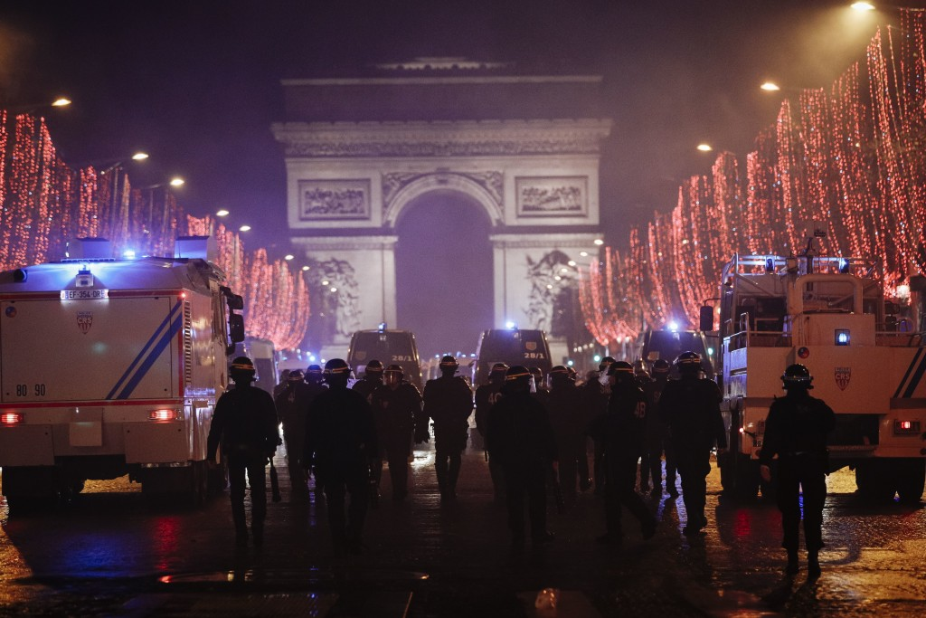 Riot police officers are seen on the Champs Elysees avenue with the Arc de Triomphe in the background, during a demonstration, in Paris Saturday, Dec....