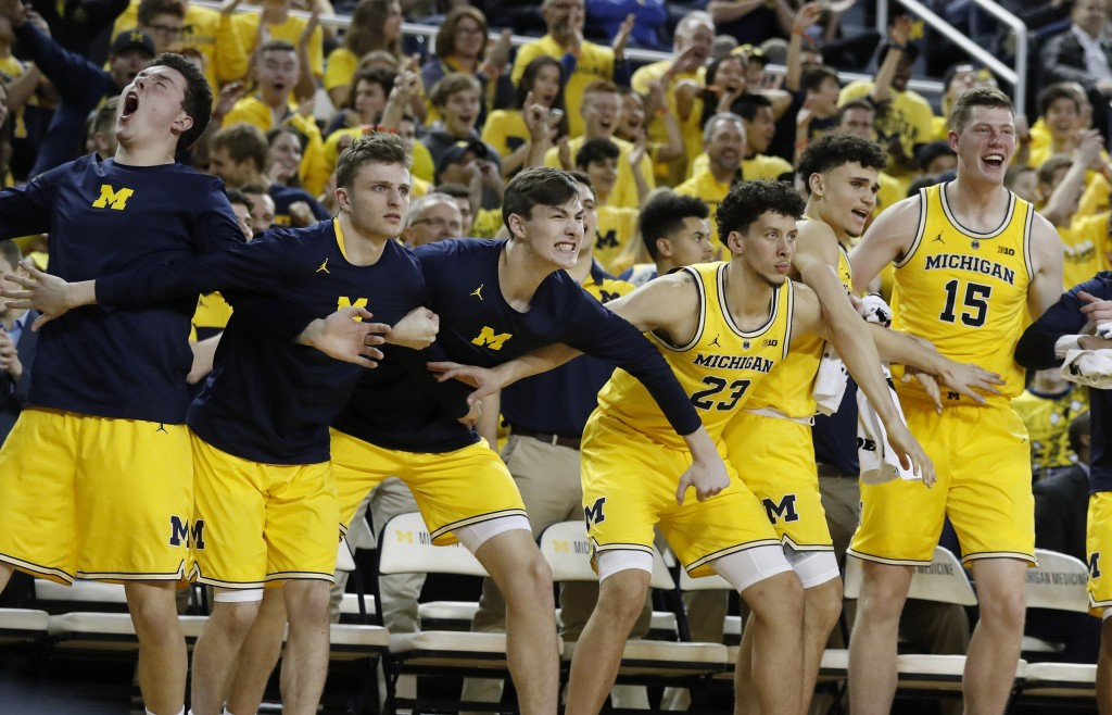 The Michigan bench reacts after a teammate's three-point basket during the second half of an NCAA college basketball game against Air Force, Saturday,...