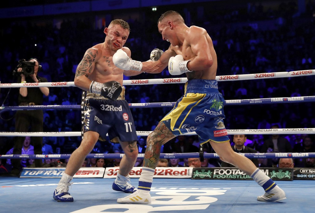 Josh Warrington, right, follows through on a right to Carl Frampton during their IBF featherweight title boxing bout Saturday, Dec. 22, 2018, in Manch...