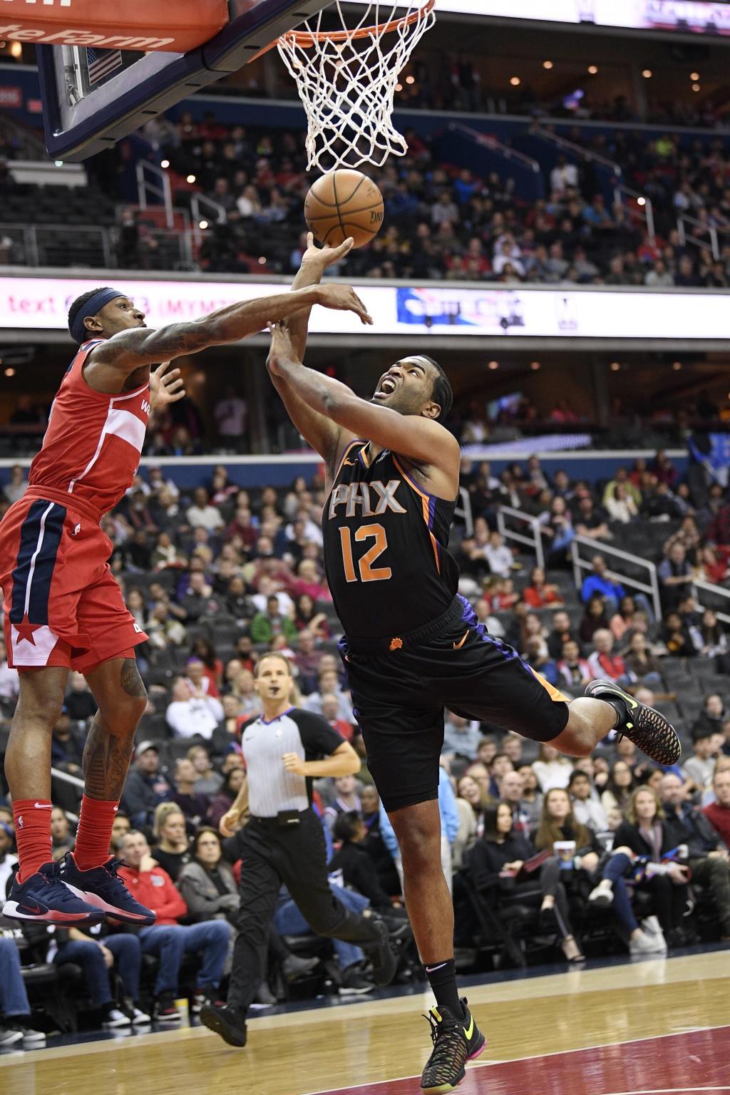 Phoenix Suns forward T.J. Warren (12) goes to the basket against Washington Wizards guard Bradley Beal, left, during the first half of an NBA basketba...